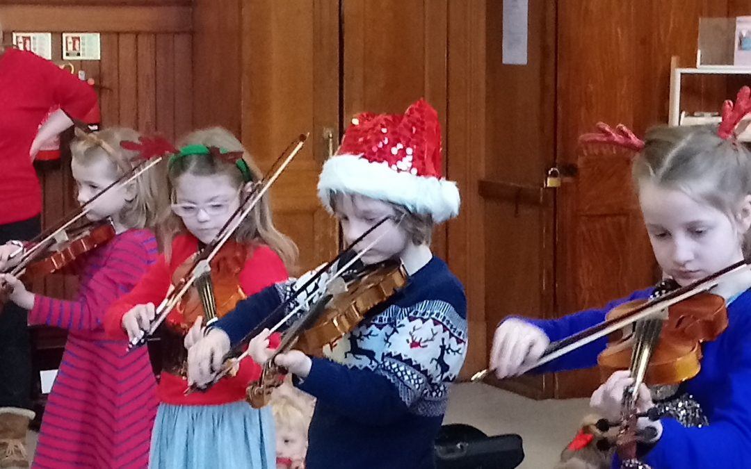 group of children in christams hats playing violin